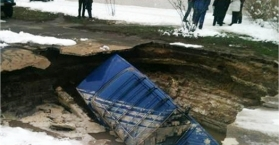 """سيارة تغور في حفرة ضخمة """"مفاجئة"""" بالعاصمة الأوكرانية كييف"""