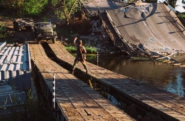 الجيش الأوكراني يعبر أحد الأنهار بجوار جسر دمره الانفصاليون الموالون لروسيا